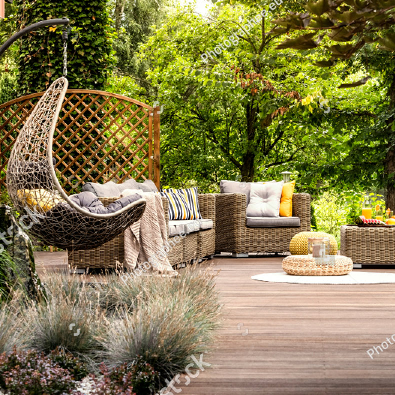 stock-photo-beautiful-wooden-terrace-with-garden-furniture-surrounded-by-greenery-on-a-warm-summer-day-1087490177s